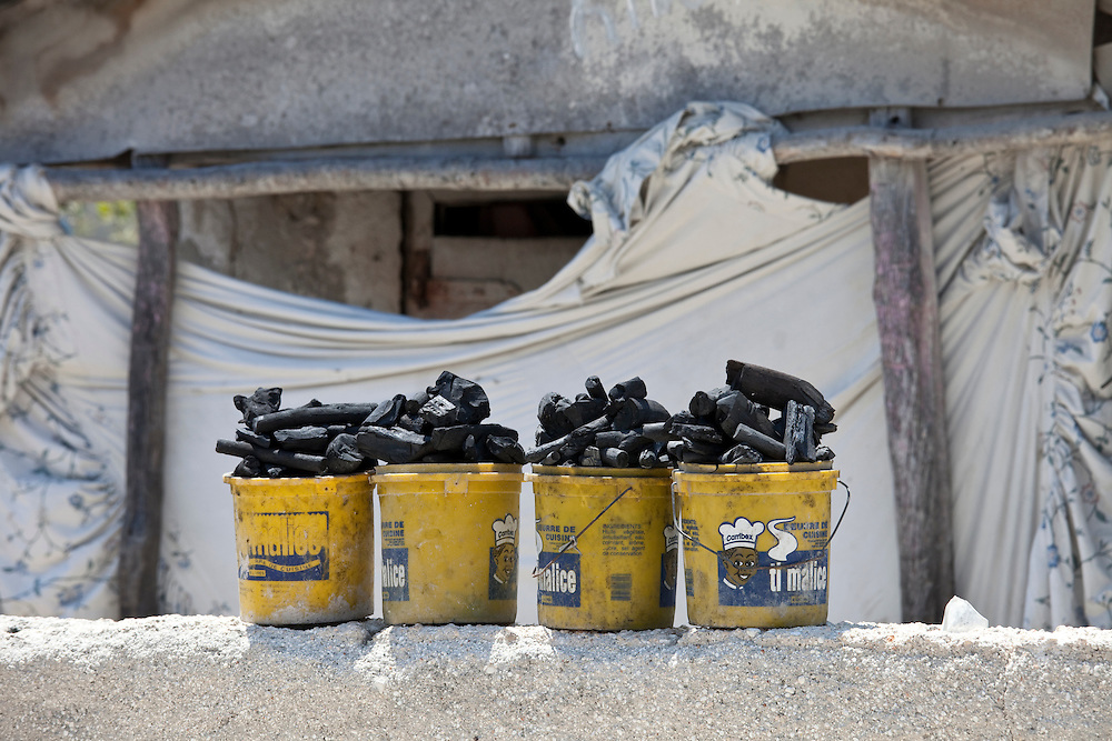 Charcoal, the primary fuel source, lined up in buckets ready to sell in Anse a Galet, Ile de la Gonave, Haiti