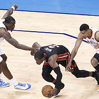 14 June 2012: Miami Heat shooting guard Dwyane Wade (3) drives by  Oklahoma City Thunder shooting guard Thabo Sefolosha (2) and Oklahoma City Thunder center Kendrick Perkins (5) during the Miami Heat 100-96 victory over the Oklahoma City Thunder, in Game 2 of the 2012 NBA Finals, at the Chesapeake Energy Arena, Oklahoma City, Oklahoma, USA.