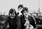 Teenage friends pose with footballs and pump after football practice, Greenford, London, UK, 1979.