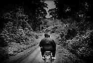Activist, Christopher Achobang rides on the back of a motorbike on the way to visit villages that abutt both the proposed Herakles Farm logging/oil palm concession and Korup National Park.  Cameroon.  The concession sits south of the road but villagers are so uniformly uninformed that even village chiefs are not sure where the Herakles Farm concession boundary sits.  There is great concern about the future for local farmers and hunters (hunting provides a necessary protein source requirement) if they are barred from access to the concession forest; or when the forest is cut down and converted to a monoculture oil palm plantation.