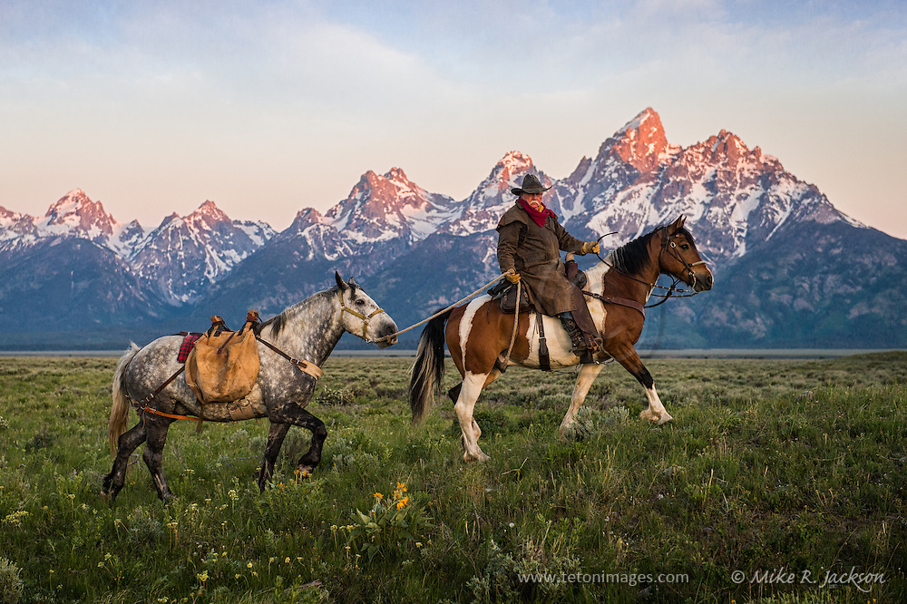 Wrangler leading his pack horse across the sagebrush flats with the majestic Grand Teton mountain range as a backdrop.