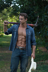 masculine muscular cowboy standing in a field with a pickaxe over his shoulder