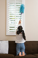 Girl (10-12) dusting window