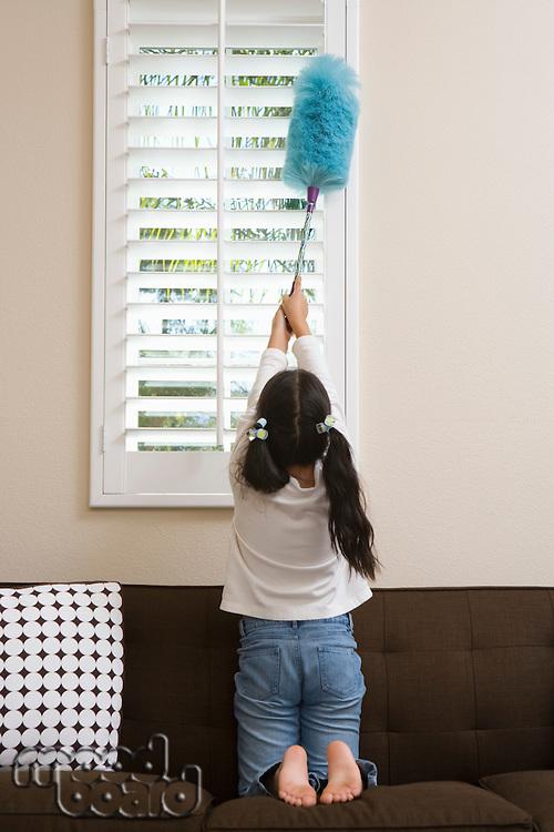 Girl (10-12) dusting window