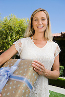 Mid-adult woman holding birthday present, smiling
