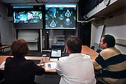 Nederland, Nijmegen, 1-12-2005Artsen,medici, in een ziekenhuis kijken naar een beeldscherm waarop collega's te zien zijn die op een andere lokatie zijn. Via een directe videoverbinding kunnen zij informatie uitwisselen en overleg plegen. Video conference.