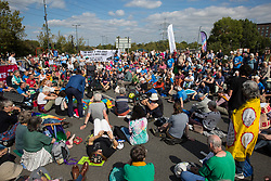 London, UK. 3 September, 2019. Hundreds of Quakers, joined by fellow peace activists and representatives of other faith groups, hold a religious service in the access road outside ExCel London as part of the day's No Faith In War activities in protest against DSEI, the world's largest arms fair.
