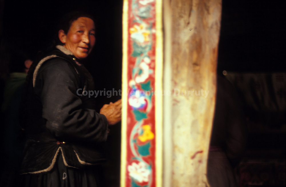 Suivant la tradition du bouddhisme tibetain, cet homme tourne autour du grand moulin a priere du temple..This man is walking around the prayers wheel according to the tibetan buddhism tradition.