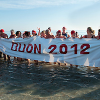 VENICE, ITALY - JANUARY 01:  Swimmers of the Ibernisti display a banner welcoming 2012 after having taken a dip in the sea on January 1, 2012 in Venice, Italy. Hundreds of people gather at Lido di Venezia to celebrate the New Year. Following a Viennese waltz, the ibernisti swimmers take a dip in the sea before celebrating on a typical combination of wine, lentils and sausage.