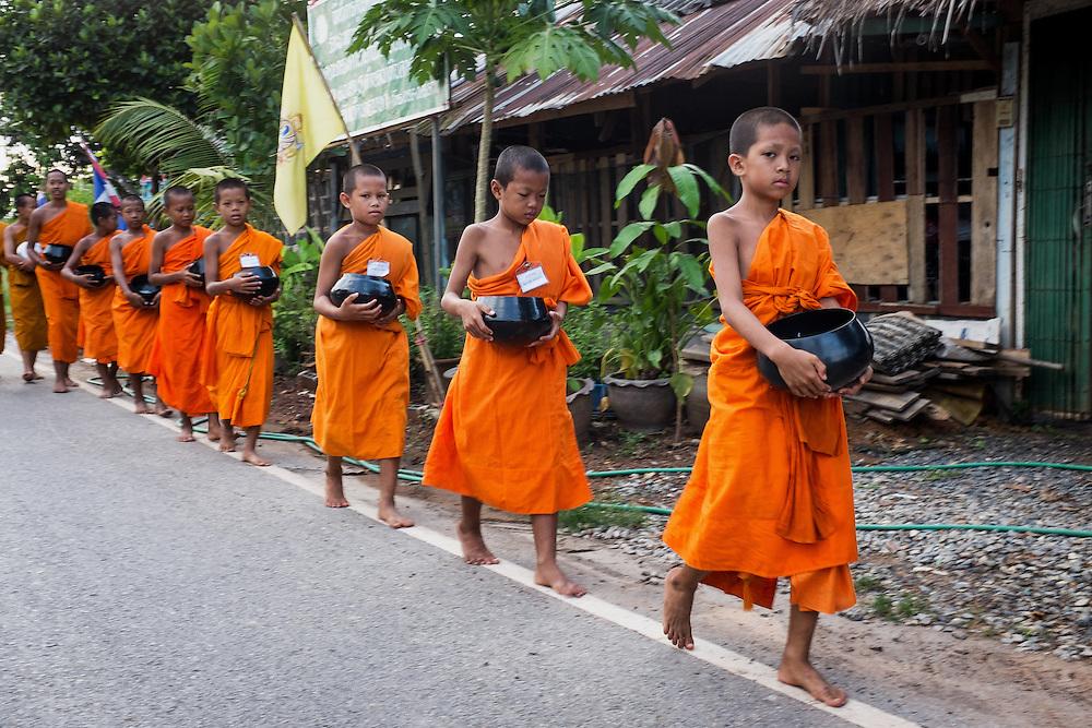 Young monks walk for alms in Nakhon Nayok, Thailand