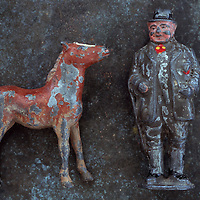 Worn lead models of rotund 19th century farmer and frisky brown foal against mottled metal background