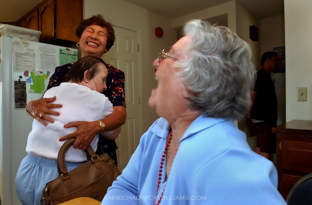 "Irene Pinole, 76, hugs Lita Acacio, her former caregiver and someone she calls ""mom"", after being reunited with her sister, Olga Johnson, right, after a 65-year hiatus."