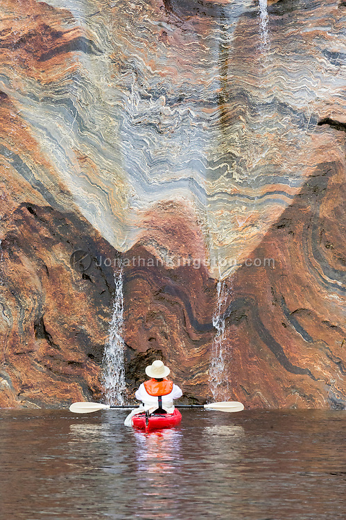 A sea kayaker inspects orange and gray metamorphosed rock in Misty fjords national monument, Alaska.