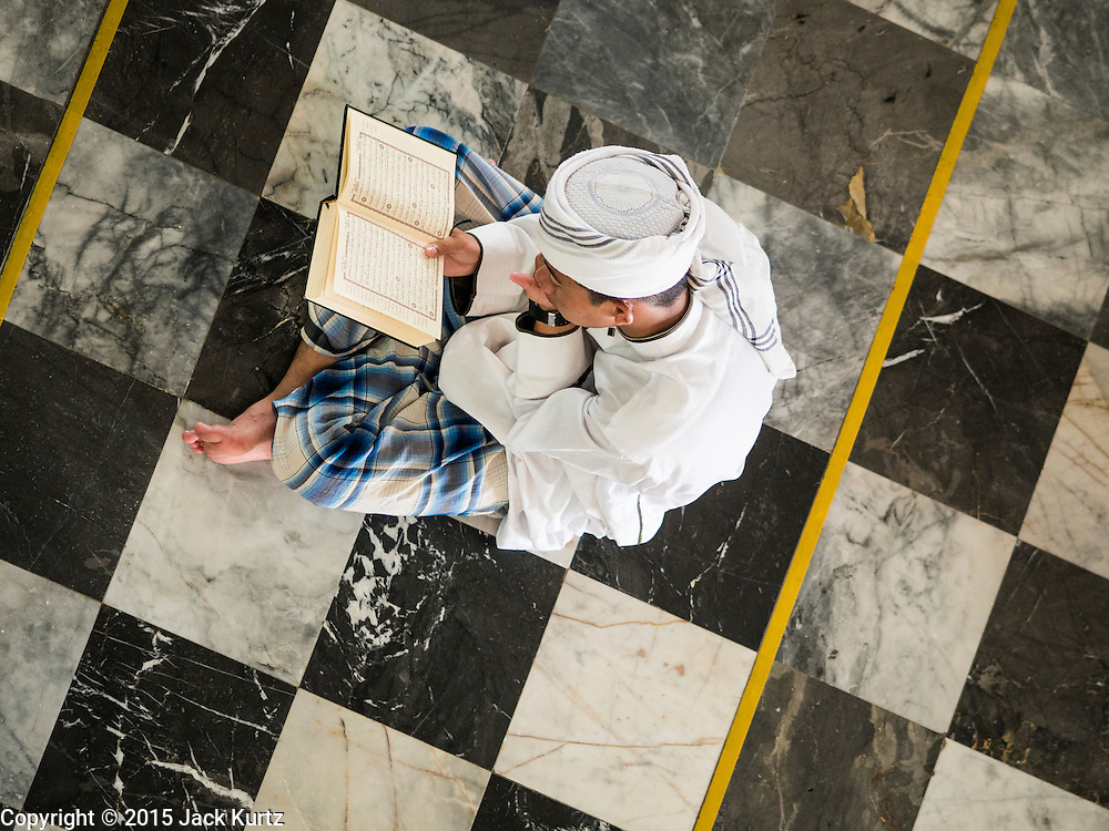 19 JUNE 2015 - PATTANI, PATTANI, THAILAND:   A man reads his Koran before Friday midday prayers in Pattani Central Mosque. Pattani Central Mosque is the main mosque in Pattani and was built in 1963. It is especially crowded during Ramadan, when the crowd frequently spills out into the street.     PHOTO BY JACK KURTZ