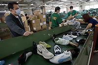 HONG  KONG, CHINA -  MARCH 22 : A Hong Kong customs agent watches counterfeit shoes being destroyed at the in Hong Kong, China on Thursday, March 22, 2007.  Among the many items that were destroyed were handbags, shoes and watches copied from many popular manufacturers such as Nike, Rolex, Gucci, Omega and Channel.  (Photo by David Paul Morris )
