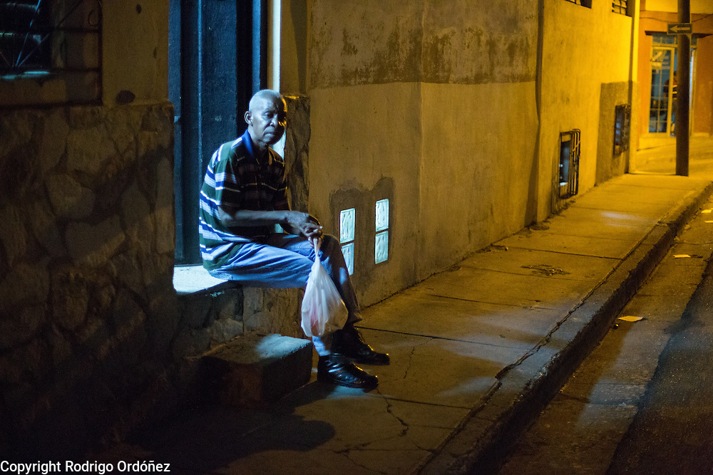 A man sits outside a home's front door in Santiago de Cuba, Cuba, on December 25, 2014.