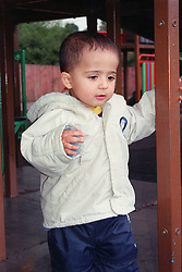 Portrait of young boy standing underneath climbing frame in children's playground,
