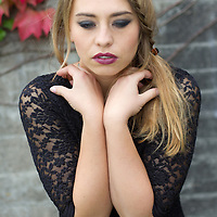 Close up of young adult female with long hair wearing a black dress looking at camera