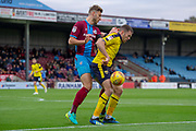 Oxford United forward Jamie Mackie holds back Scunthorpe United defender Charlie Goode during the EFL Sky Bet League 1 match between Scunthorpe United and Oxford United at Glanford Park, Scunthorpe, England on 3 November 2018.