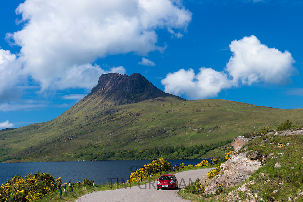 Motorist on touring holiday passes Stac Pollaidh, Stack Polly, mountain, within Inverpolly National Nature Reserve in Coigach area of North West Highlands Geopark, Scotland