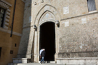 SIENA, ITALY - 20 MARCH 2015: Two men step inside the headquarters of the Monte dei Paschi di Siena bank at Palazzo Salimbeni in Siena, Italy, on March 20th 2015. <br /> <br /> Siena, a Tuscan city and UNESCO World Heritage Site, is home to Monte dei Paschi di Siena, the world's oldest surviving bank and Italy's third largest bank. The bank, founded in 1472, was the largest employer in Siena, and it helped finance a host of community projects and services until it stumbled during the financial crisis started in 2008.