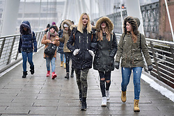"""© Licensed to London News Pictures. 18/03/2018. LONDON, UK.  Tourists and Londoners on Hungerford Bridge are caught in a late afternoon blizzard as the mini """"beast from the east"""" weather system continues to bring frigid weather to the UK.  Photo credit: Stephen Chung/LNP"""