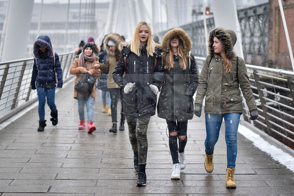 "© Licensed to London News Pictures. 18/03/2018. LONDON, UK.  Tourists and Londoners on Hungerford Bridge are caught in a late afternoon blizzard as the mini ""beast from the east"" weather system continues to bring frigid weather to the UK.  Photo credit: Stephen Chung/LNP"