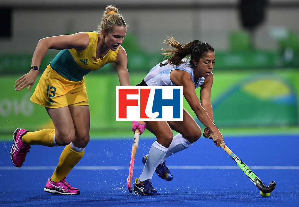 Australia's Edwina Bone (L) chases Argentina's Gabriela Aguirre during the women's field hockey Australia vs Argentina match of the Rio 2016 Olympics Games at the Olympic Hockey Centre in Rio de Janeiro on August, 11 2016. / AFP / MANAN VATSYAYANA        (Photo credit should read MANAN VATSYAYANA/AFP/Getty Images)