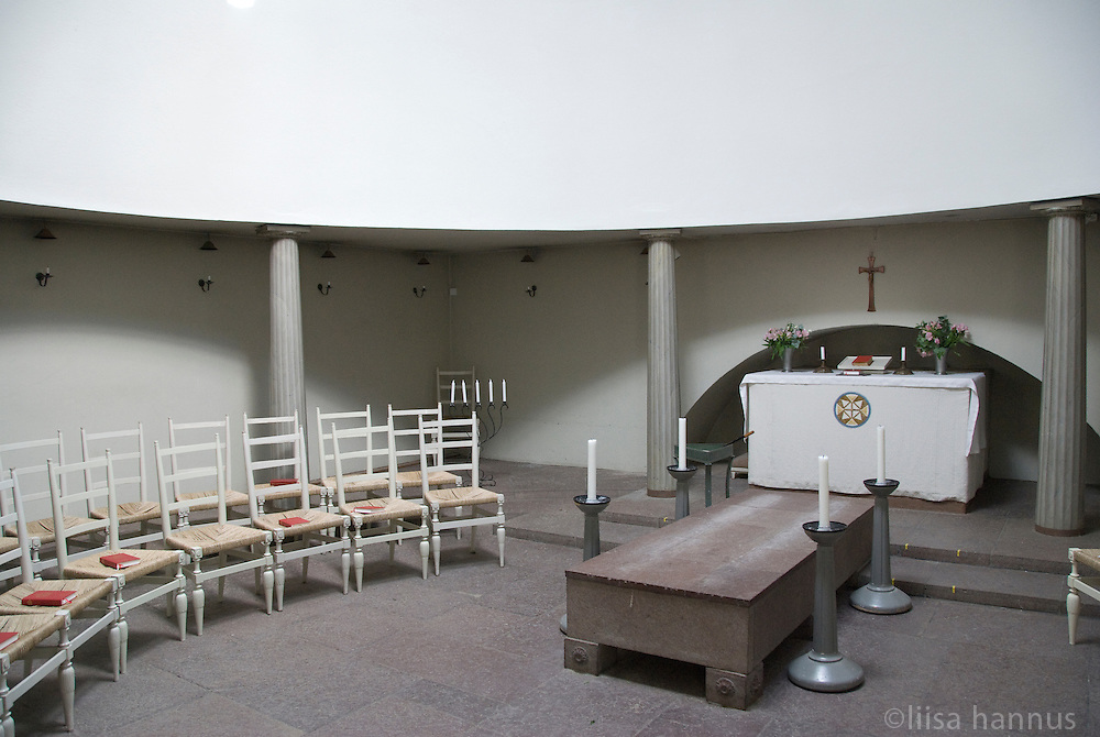 Inside the Woodland Chapel, chairs are arranged in a circular pattern. Designed by Gunnar Asplund, the chapel's exterior is square and dark, but inside mourners sit in a circle and are flooded with light coming in from the cupola in the roof.