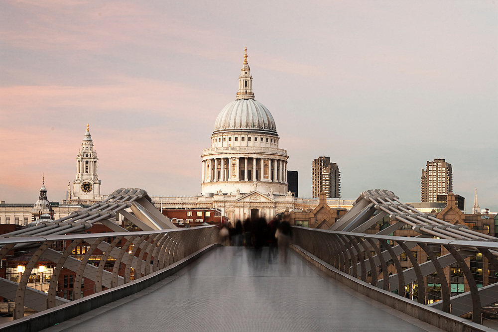 Commuters crossing the Millenium Bridge walking towards St Pauls Cathedral