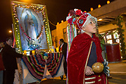 A young boy dressed as a Matachin warrior escorts the likeness of the Virgin Mary during a procession from the Cathedral Basilica of St. Francis of Assisi celebrating our Lady of Guadalupe December 11, 2015 in Santa Fe, New Mexico. Guadalupanos as the devotees are known, celebrate the apparitions of the Virgin Mary to an Aztec peasant at Tepeyac, Mexico in 1531.