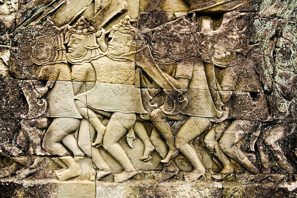 Angkor Thom, Bayon temple, wall relief with scenes of battle between Khmer and Cham warriors using elephants, horses, chariots, and various weapons.  They wear tunics and fitted shorts, with bare feet.