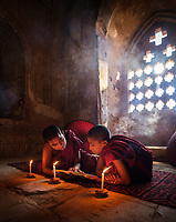 BAGAN, MYANMAR - CIRCA DECEMBER 2017: Monks inside a temple reading a book around candelights on a temple in Bagan
