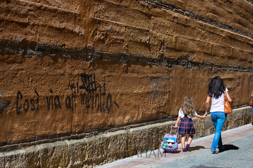 Spanish woman taking child to school in Calle Sacramento in Leon, Castilla y Leon, Spain