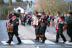 "© Licensed to London News Pictures.10/1/2015.Sharnford, Leicestershire, UK. The annual plough tour by the Hinckley Bullockers took place today. Pictured, crossing the Leicester road on the way to the Sharnford Arms. Visiting seven venues around Leicestershire the Bullockers, some with with red painted faces, are seen pulling their decorated plough along the street before stopping to perform traditional dances.<br /> <br /> HISTORY -  On the first Monday after Twelfth Night - Plough Monday - the plough was prepared for the new season, dressed in gaudy ribbons and taken in procession around the villages. In South West Leicestershire the men pulling the plough, who ""raddled"" their faces, were known as Plough Bullocks and were aided and abetted by dancers who danced dances peculiar to the Eastern Counties. The Plough Bullocks and the Molly Dancers were last seen in this area at the turn of the century in Sapcote.<br />  Traditionally, the Plough Bullockers would stop at public houses, farms and large houses, dance and/or sing and demand recognition in the form of cash donations or drink. If neither was forthcoming the offending landlord's drive was ploughed up. Photo credit : Dave Warren/LNP"