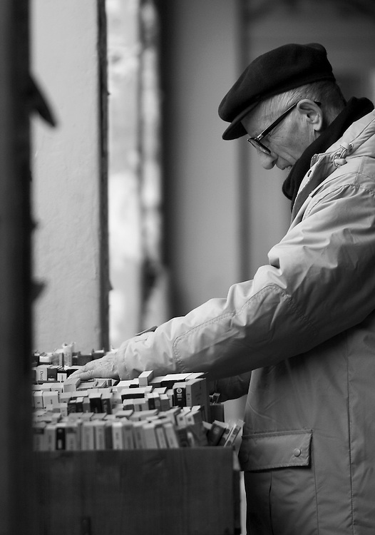 Black and white photography.Man looking for books on bookmarket in Bologna.