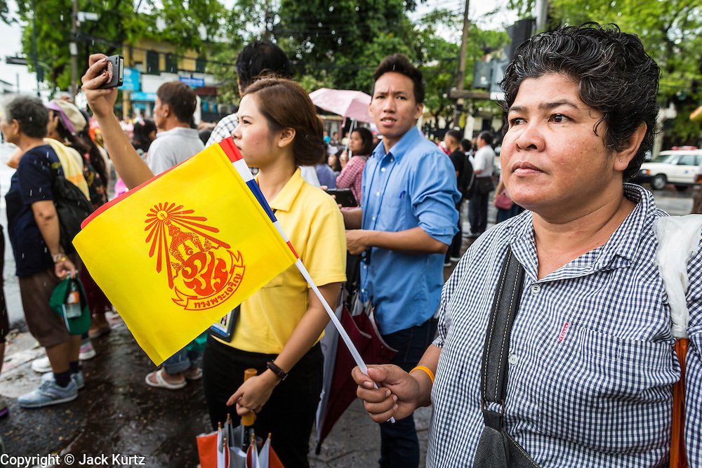 "05 MAY 2013 - BANGKOK, THAILAND:   A woman waves the royal flag while she waits to see Bhumibol Adulyadej, the King of Thailand, Sunday. The King and Queen, who are both hospitalized and in poor health, did not attend Sunday's event. May 5 marks the 63rd anniversary of the Coronation of His Majesty King Bhumibol Adulyadej. The day is celebrated as a national holiday; since this year it falls on a Sunday, it will be observed on Monday May 6, and as such all government offices and commercial banks will close for the day. HM King Bhumibol Adulyadej is the longest reigning monarch in the world. Each year on the 5th of May, the Kingdom of Thailand commemorates the day when, in 1950, the Coronation Ceremony was held for His Majesty King Bhumibol Adulyadej, the 9th in the Chakri Dynasty (Rama IX). On the 5th of May, His Majesty conducts a merit making ceremony, presenting offerings to Buddhist monks, and leads a ""Wien Thien"" ceremony, walking three times around sacred grounds at the Temple of the Emerald Buddha.    PHOTO BY JACK KURTZ"