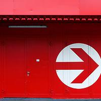 The photograph of a facade with a large circular arrow.