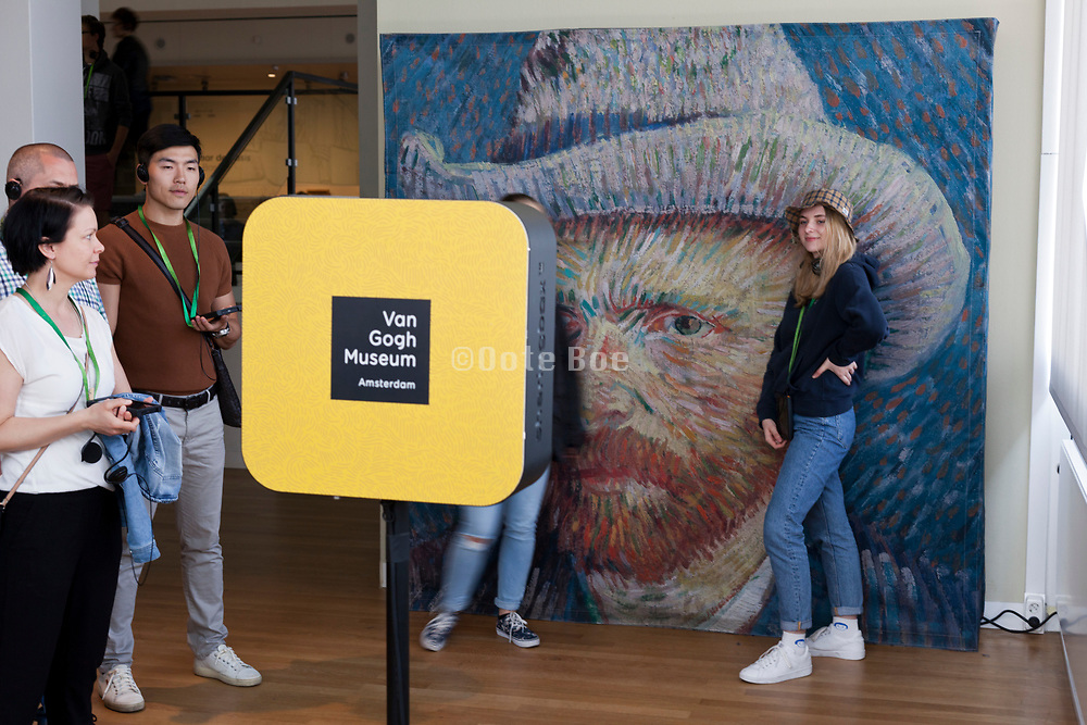 tourists using the social media selfies camera with a large painting poster at the Van Gogh Museum