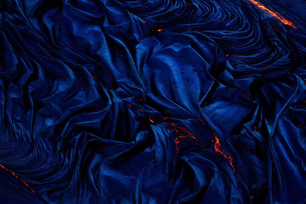 The surface of a river of molten pahoehoe quickly solidifies, and friction from the faster moving lava beneath creates an abstract of folds and wrinkles, while the deep blue hues are a result of the low amount of ambient light. Aerial charter service provided by Paradise Helicopters.