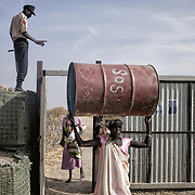 Des gardiens de la société de surveillance privée « Warriors » filtrent les entrées et sorties du camp de protection des civils de la mission des Nations Unies au Soudan du Sud, Minuss, de Malakal. Sur les affiches, des portraits de personnes interdites d'entrée pour raisons de sécurité. Certaines femmes de l'ethnie shilluk s'autorisent à se rendre quotidiennement dans la ville de Malakal pour commercer, avant de rentrer au camp le soir. Les dangers inhérents à une telle entreprise (agressions, viols, pillages...) les obligent à se déplacer en petits groupes.