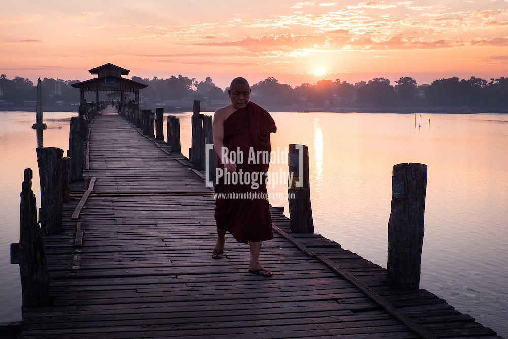 A monk walks at sunrise across the wooden U Bein's Bridge near Amapura in Mandalay.