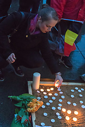 Trafalgar Square, London, March 24th 2016. A woman lays a candle as people gather in London's Trafalgar Square to light candles and lay flowers in memory of those who lost their lives in the Brussels terror attacks on March 22nd in which 31 people were killed and dozens injured.