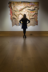 "Bonhams, Mayfair, London. A woman admires ""Peju's Robe"", estimated at £450,000 - 550,000, by Ghanaian sculptor El Anatsui is made from thousands of pressed bottle tops to be auctioned at Bonhams post-war and Contemporary art sale.  ///FOR LICENCING CONTACT: paul@pauldaveycreative.co.uk TEL:+44 (0) 7966 016 296 or +44 (0) 20 8969 6875. ©2015 Paul R Davey. All rights reserved."