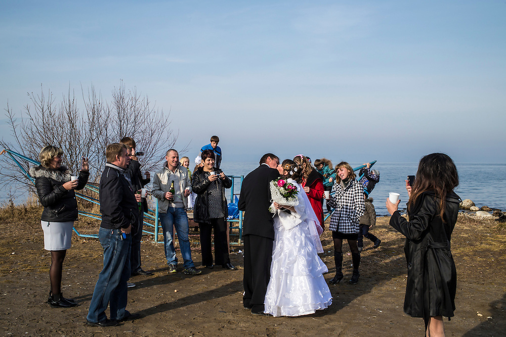 Tatiyana and Nikolai, surrounded by friends and family, kiss on the shore of Lake Baikal on their wedding day on Friday, October 25, 2013 in Baikalsk, Russia.