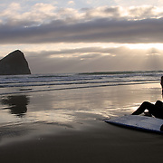 A surfer watches the sunset at Pacific City, Oregon.  Haystack Rock is in the background.