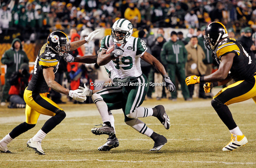 New York Jets wide receiver Jerricho Cotchery (89) gets tackled by Pittsburgh Steelers cornerback Ike Taylor (24) and Pittsburgh Steelers linebacker Lawrence Timmons (94) after catching a first down pass on third and one that gives the Jets first and goal during the fourth quarter of the NFL 2011 AFC Championship playoff football game against the Pittsburgh Steelers on Sunday, January 23, 2011 in Pittsburgh, Pennsylvania. The Steelers won the game 24-19. (©Paul Anthony Spinelli)