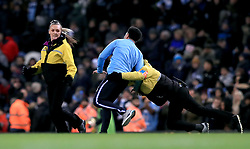 Security tackle a pitch invader at the end of the match