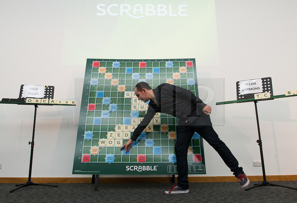 © Licensed to London News Pictures.03/11/2013. London, UK. Brett Smitheram former champion comments the player's move to the audience during the final of The National Scrabble Championship between Paul Alland and Allan Simmons. Paul Allan, a teacher from Rushden, Northamptonshire, previously crowned champion in 2007 while Allan Simmons, a Scrabble consultant from Coldingham Village in the Scottish Borders, was previously crowned National Scrabble Champion in 2008.Photo credit : Peter Kollanyi/LNP