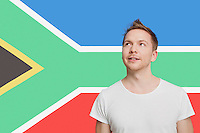 Young Caucasian man in white t-shirt day dreaming against South African flag